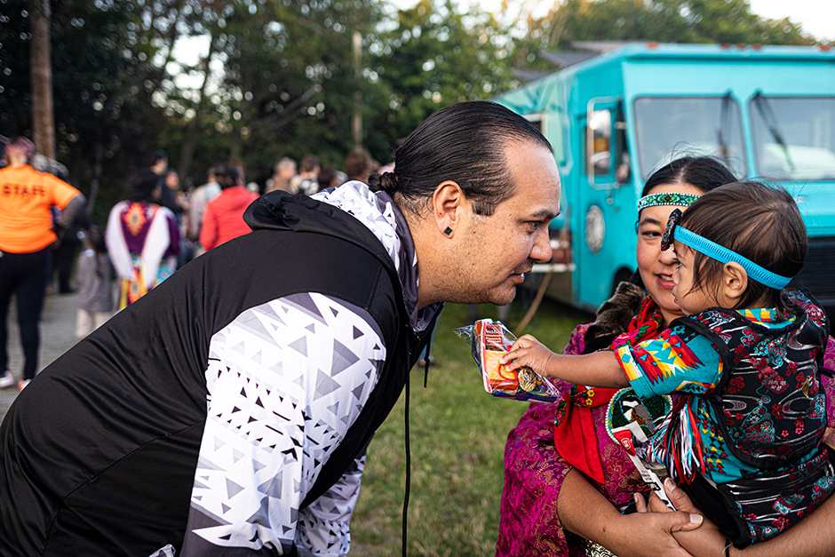 Iisaaksiichaa greets his sister and nephew at the powwow at Daybreak Star Cultural Center in Seattle.