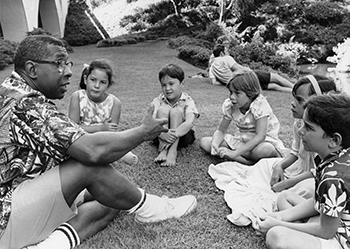 Spencer Shaw speaks with a group of children