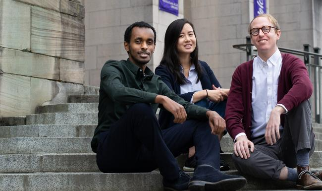 MSIM '19 graduates Amir Ali, Tiffany Ku and Kevin McCraney seated on the steps of Suzzallo Library