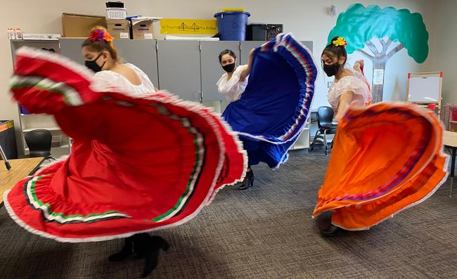 Dancers in traditional garb perform a Mexican folk dance.